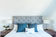 A contemporary bedroom with a gray tufted headboard and blue pillows.