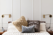 Tall wainscot behind white bedding and matching swing-arm lights.