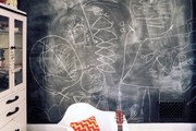 A white molded-plastic chair and a striped rug in a room with a chalkboard wall