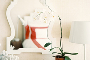 A white mirror hung on grass-cloth wallpaper