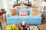 A blue couch with patterned pillows paired with a black-and-white coffee table