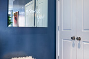 A blue accent wall with a mirror and furry pouf.