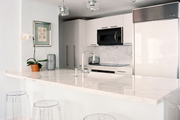 A modern kitchen with white marble and Lucite bar stools