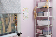 A pelmet box window treatment, industrial-style bookshelf, and skirted storage bench fill a pink nursery