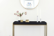A side table with gold and black accents and a circular mirror hanging above.