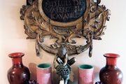 Turtle candlesticks and decorative vases below an ornate piece of art