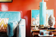 A blue lamp atop wooden nesting tables in front of red walls
