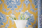 A white vase of flowers against a wall of toile