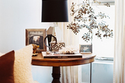 A round end table beside a gold tree sculpture