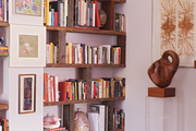 Built-in shelves of books surrounded by artworks