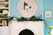 A portrait of a dog above a mantel decorated for the holidays
