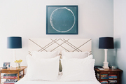 An upholstered headboard embellished with a geometric nailhead design
