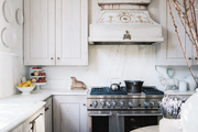 A kitchen with white cabinetry and a stainless steel range