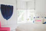 Minimalist window-lit bedroom with large-scale art and pink and blue accents.