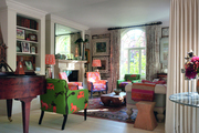 Armchairs, curtains, and lamp shades, all in patterned fabrics, in a living space