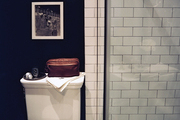 A mixture of subway tile and penny tile in a black-walled bathroom