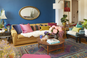 An eclectic living room with lots of colors, flowers and accessories.