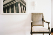 A French-style chair next to framed art
