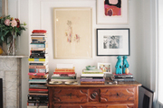 Artwork and a book collection arranged with a wooded storage piece