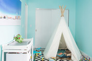 Indoor tipi with patterned area rug and activities for kids.