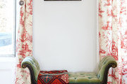 Red and white toile drapes flank a tufted green bench
