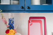 Colorful cutting boards sit below bright blue kitchen cabinetry.