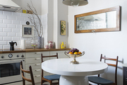A kitchen's eating area; midcentury dining chairs and a pedestal table