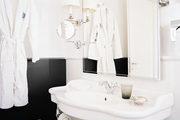 A black-and-white bathroom with a pair of sconces with white shades