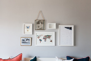 Small framed pieces of art hanging on grey walls above colorful throw pillows.