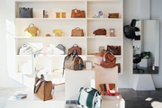 Leather handbags on white pedestals of varying heights