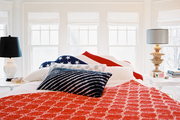 A flag-motif headboard and bedding in a color palette of red, white, and blue