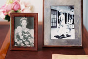 Framed black-and-white photos, including a portrait of Queen Elizabeth II