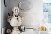 A bust and an arrangement of hanging plates in a white kitchen