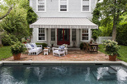 A brick patio beside an in-ground pool in Sag Harbor