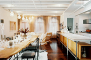 A long live-edge dining table with mix-and-match chairs parallels a kitchen peninsula