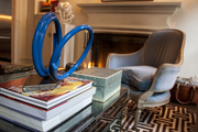 A piece of coiled artwork on a book-covered coffee table