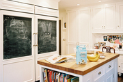 A kitchen with chalkboard panels on white refrigerator doors