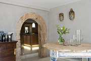 A stone arch leads into a clean-lined area featuring global art, a sideboard, and table
