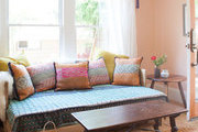 A Bohemian sitting area with colorful quilts and pillows.