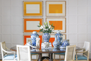 A dining room with a round table, a collection of chinoiserie vases, and six Donald Judd prints