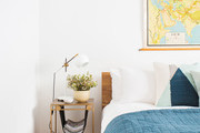 Contemporary and bohemian white and blue bedroom with map above the bed.
