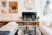 A round mirror above a fireplace surrounded by white furniture and a zebra-print rug