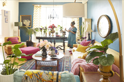 A living room with bold colors and lots of plants and flowers.