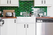 A contemporary kitchen with green tiles and an antique rug.