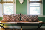 A pair of brown patterned pillows atop a bench in  a green-walled room