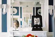 A white marble mantel styled with a Buddha-head statue and framed art