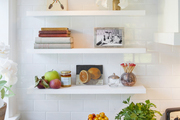 Colorful decor in white tiled kitchen.