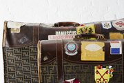A duo of vintage suitcases covered in stickers from around the world