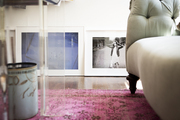 A couch atop an area rug and photographs leaning against a wall in a work space
