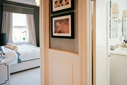 Framed art in a hallway with gray walls